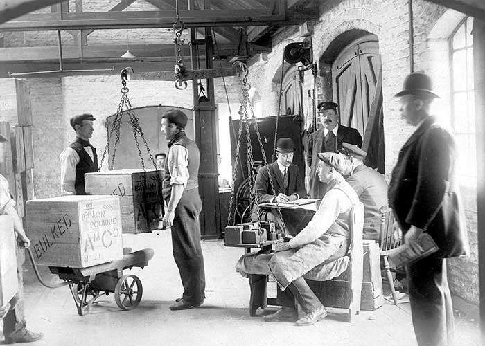 DOCK WORKERS CHECKING THE WEIGHT OF BOXES C1910..jpg