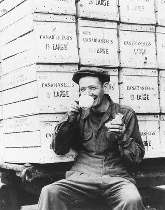 London Surrey Commercial Docks worker drinking tea, surrounded by crates of eggs from Canada about a year after the end of WWII 1946 .   X.jpg