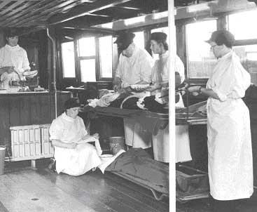 River Emergency Service 1939-41.A Doctor gives the 'patient' an injection,the nurses and crew are giving a demonstration of the ship and its operating theatre and other facilities for dealing with casualties.jpg