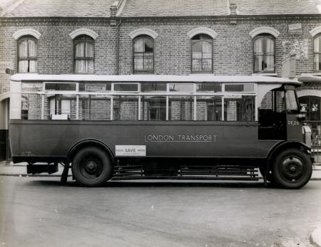 View of single deck DE-type bus, no DE28, 1934. parked near  the Old Kent Road Gararge.   X.png