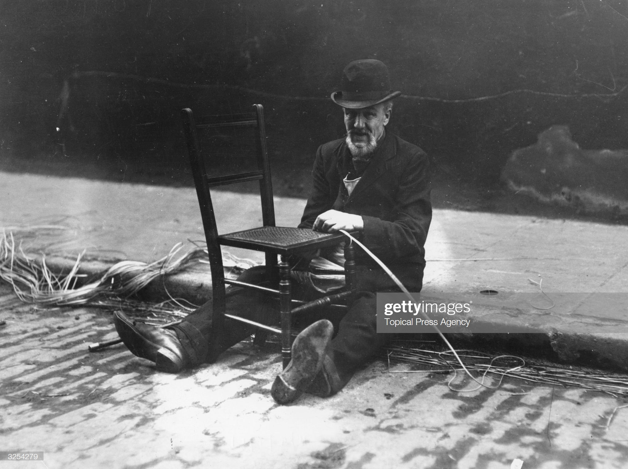 Tabard Street. A chairmender at work re-weaving the seat of a chair in Tabard Street c1911.  X.png