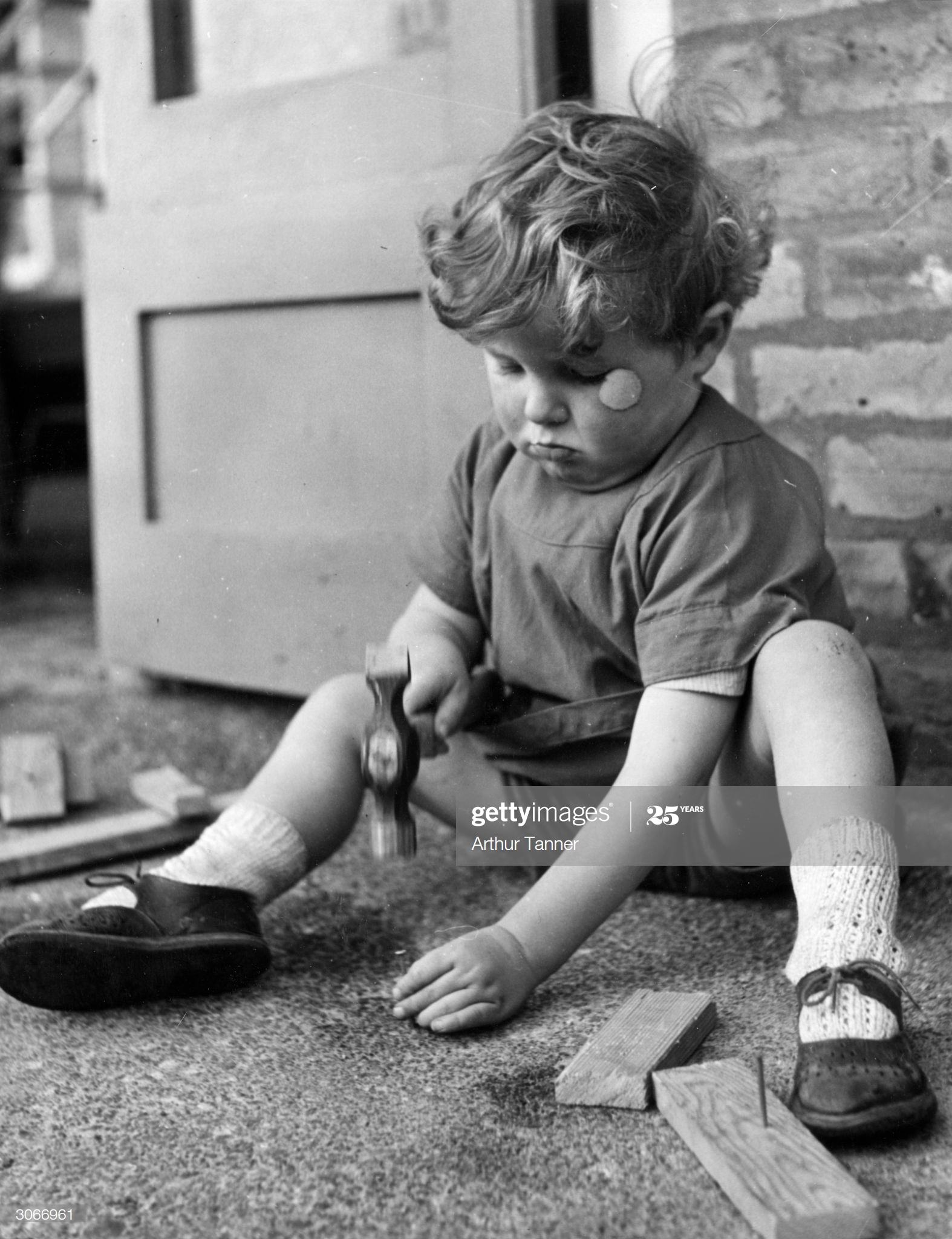 Grange Road, Kintore Way, Bermondsey, 1936. A little boy plays with hammer and nails at the nursery school.  X.png