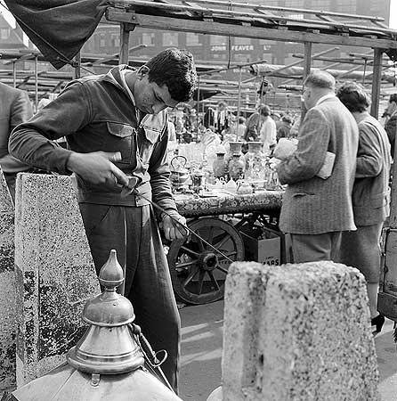 Bermondsey Antiques Market. A young man examining a sword, with the John Feaver factory on Tower Bridge Road visible in the background.  X.png
