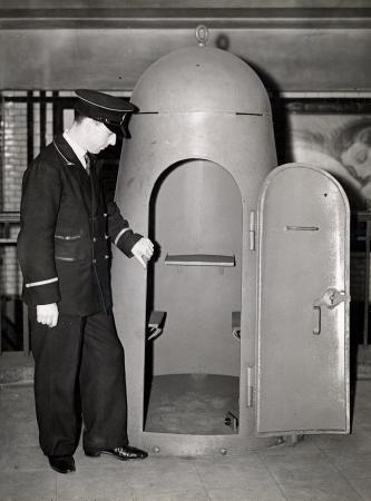 WW2. Small two-person air-raid shelter, a member of uniformed staff looks on, c1935.  X.png