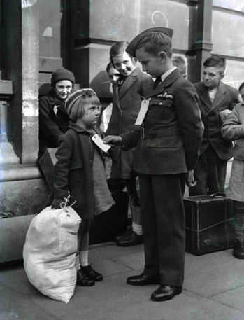 World War Two, 10th, September 1942. Brian Lee wearing his RAF uniform studies the evacuation label on a, model evacuee, Alice King aged 5, from Rotherhithe.  X.png